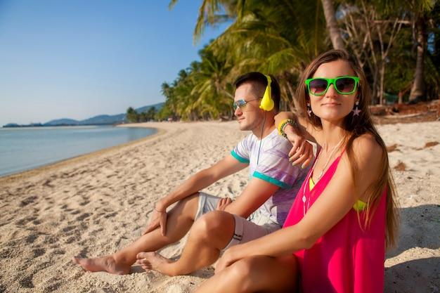 Молодая хипстерская влюбленная пара, тропический пляж, отдых, летний модный стиль, солнцезащитные очки, наушники