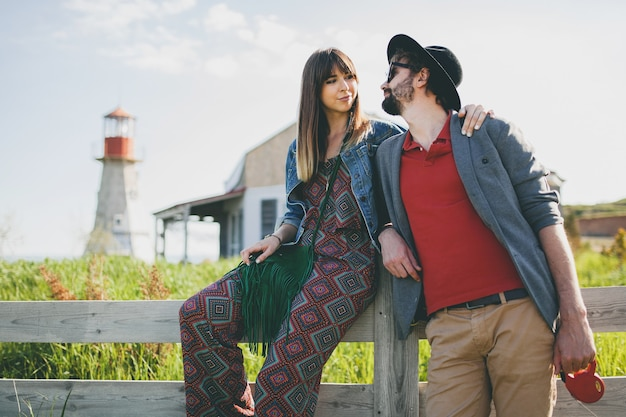 田舎を歩く愛の若い流行に敏感なカップルのインディースタイル
