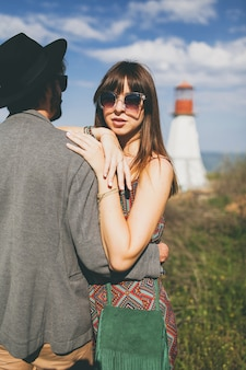 Young hipster couple indie style in love walking in countryside, lighthouse on background