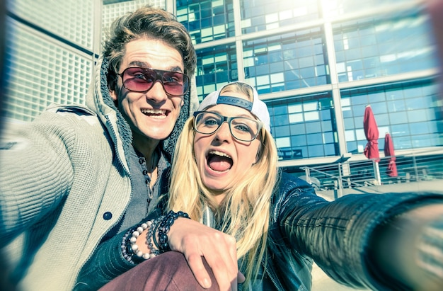 Young hipster couple in love taking a funny selfie in urban city background