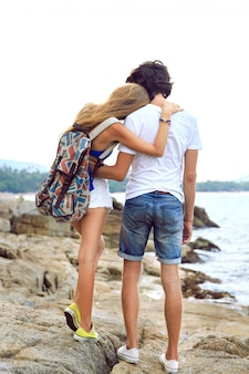 Young hipster couple in love travel together in summer time, posing at amazing beautiful stone beach, wearing stylish casual outfits, hugs and having fun.