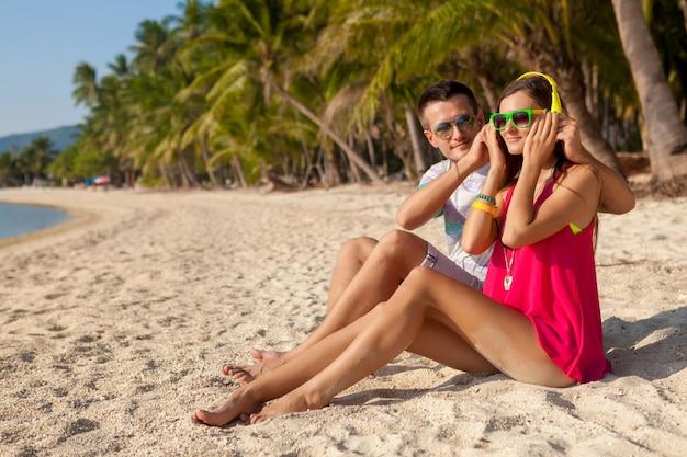 Coppia giovane hipster in amore, spiaggia tropicale, vacanze, stile alla moda estivo, occhiali da sole, cuffie