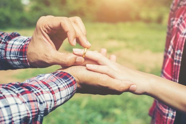 自然の中で婚約指輪を身に着けている若いヒップスターカップル、甘いと