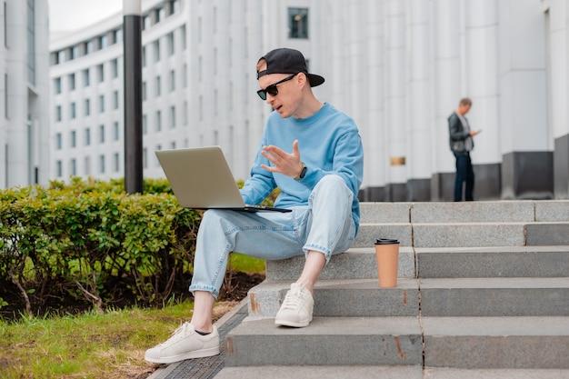 Молодой хипстерский модный бизнесмен в солнцезащитных очках сидит на лестнице бизнес-центра с чашкой кофе и использует ноутбук