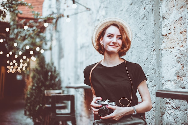 若い流行に敏感な女性ジャーナリストが椅子に座っているし、屋外で笑顔