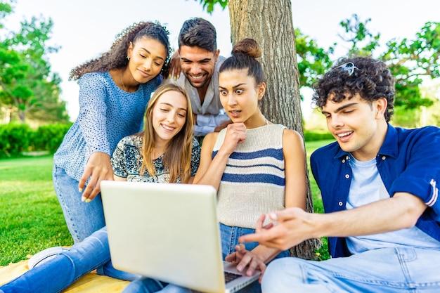 流行に敏感な若い友人グループが都市公園の芝生に座って、ノートパソコンの画面を見て驚きの顔をしています。新しいトレンドとテクノロジーに関するミレニアル世代とのモダンで楽しいコンセプト。ワイヤレスおよびソーシャルメディア