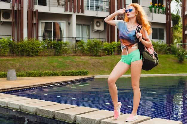 Молодая хипстерская рыжая стройная женщина, идущая в тренажерный зал, красочные красные волосы, синие солнцезащитные очки, спортивный стиль, веснушки, родимые пятна, рюкзак, счастливый, игривый, крутой наряд, улыбающийся, чувственный, спортивный, фитнес-одежда