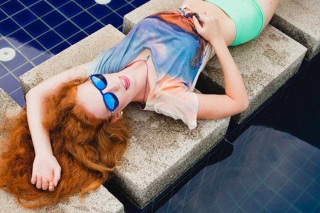 Молодая хипстерская рыжая стройная женщина, лежащая в бассейне, вид сверху, красочные красные волосы, синие солнцезащитные очки, спортивный стиль, веснушки, родинки, расслабленная, счастливая, игривая, классная одежда, улыбающаяся, чувственная