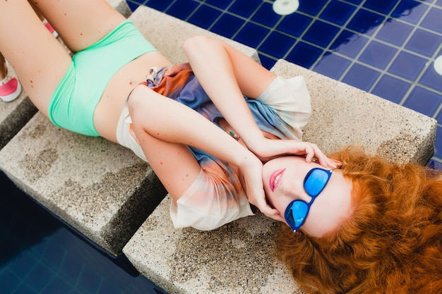 Young hipster ginger slim woman lying at pool, view from above, red hair colorful, blue sunglasses, sport style, freckles, birthmarks, relaxed, happy, playful, cool outfit, smiling, sensual