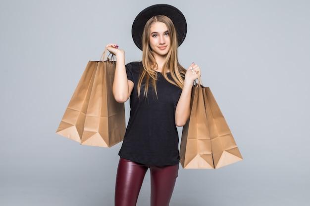 黒のtシャツと白で隔離されるハンドルを持つ空白のクラフトショッピングバッグを保持している革のズボンで着飾った内気な少女