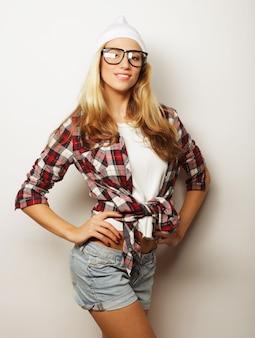 젊은 힙스터 소녀는 재미 있고 미쳐가고, 안경 모자와 밝은 화장을 하고 있습니다. 흰 바탕.