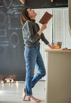Битник молодая девушка читает книгу дома. обучение, студент готовится к экзамену. старинная книга раритет антиквариат. свободное место. мелованная доска с рамками. место для макета текста