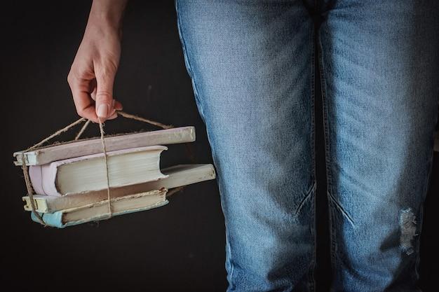 若い流行に敏感な女の子は家で本を読んでいます。トレーニング、学生は試験の準備をします。古書希少アンティーク。ジーンズぼろぼろの本
