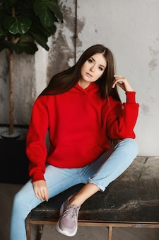 Young hipster girl in a red hoodie and blue jeans posing in the loft interior