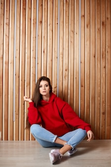 A young hipster girl in a red hoodie and blue jeans sits on the floor over a wooden wall.