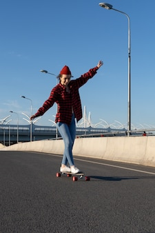 Young hipster girl skateboarding on city road happy enjoy longboard ride youth and urban lifestyle