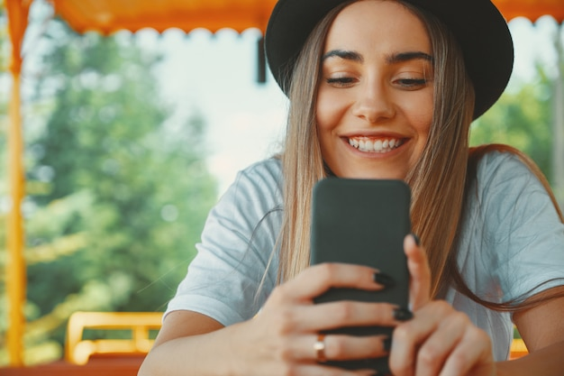 Young hipster girl in trendy hat holding smartphone in hands