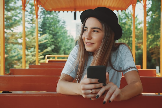 Young hipster girl in trendy hat holding smartphone