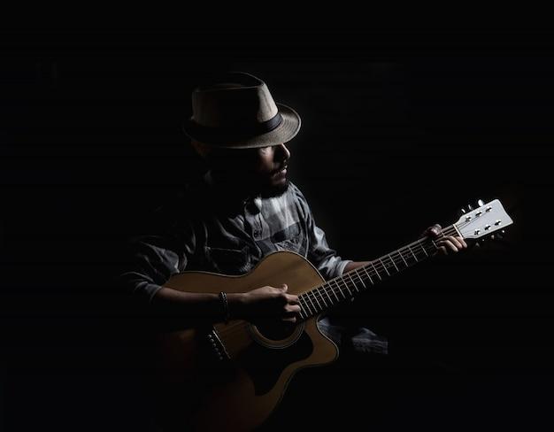 젊은 hipster 기타리스트 어쿠스틱 기타에서 재생합니다.