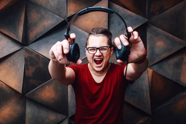 Young hipster guy in glasses with headphones