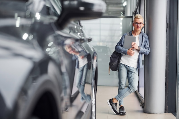 Young hipster guy in nice clothes stands indoors and near car