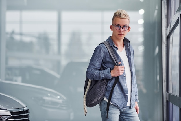 Young hipster guy in nice clothes stands indoors near modern car