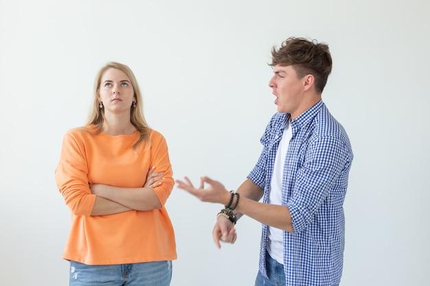若い流行に敏感な男は、白い背景の上の彼の最愛の女の子に手を上げて叫びます。のコンセプト