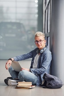 Young hipster guy sitting indoors with laptop and books