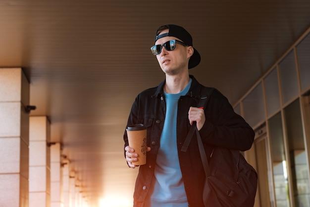 젊은 hipster 남자 컵 커피 현대 거리 유리 복도 들고 도시 거리 검은 모자 스탠드