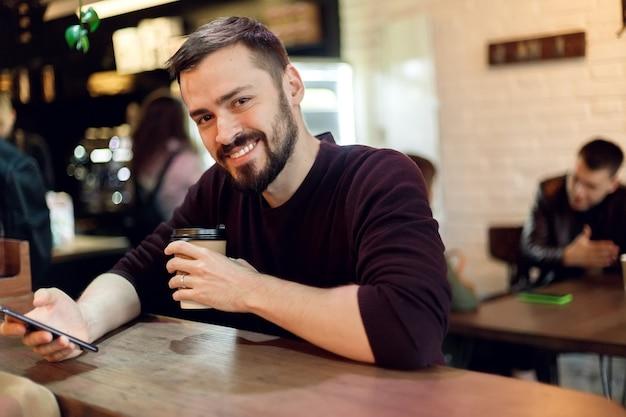 バーで彼の携帯電話でテキストメッセージを送信し、カプチーノを持っている若い流行に敏感な男。昼食時にシティカフェでエスプレッソコーヒーを飲み、タブレットコンピューターで作業している若いファッション男/流行に敏感な男