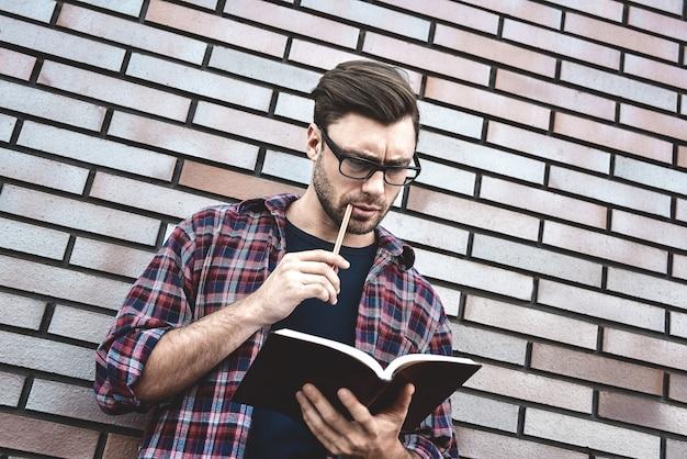 Молодой хипстерский парень в очках, читая книгу или записную книжку, делает некоторые заметки и идеи на фоне кирпичной стены.