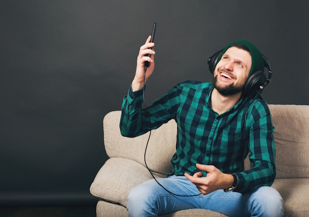 Uomo barbuto bello giovane hipster seduto su un divano a casa, ascoltando musica in cuffia, guardando smartphone, camicia a scacchi verde, intrattenimento