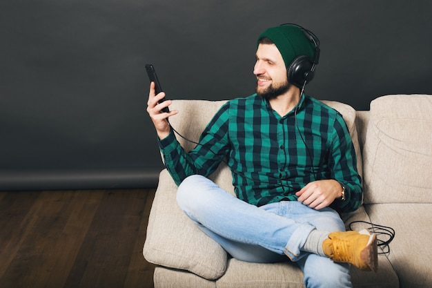 Молодой битник красивый бородатый мужчина сидит на диване у себя дома, слушает музыку в наушниках, смотрит смартфон, зеленая клетчатая рубашка, развлечения