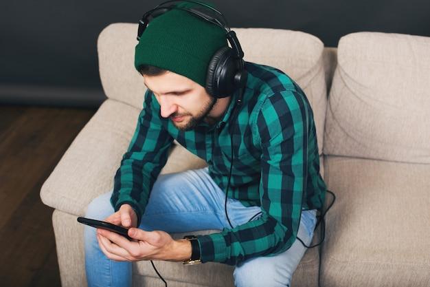 Молодой битник красивый бородатый мужчина сидит на диване у себя дома, слушает музыку в наушниках