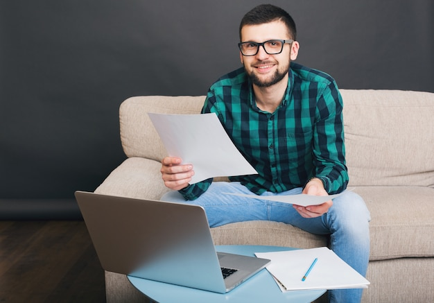 Молодой битник красивый бородатый мужчина, сидя на диване у себя дома