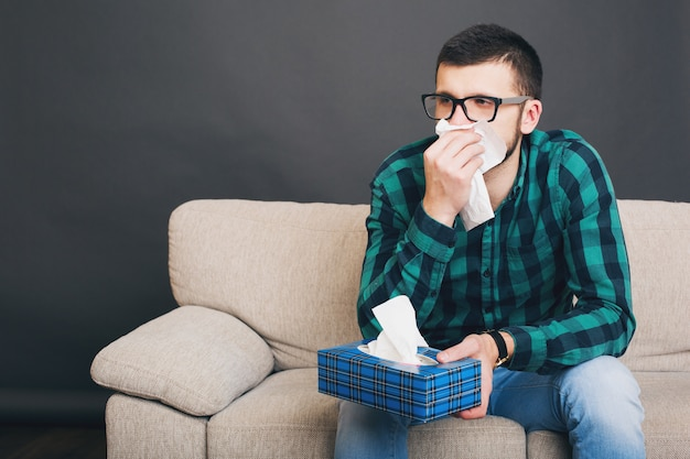 Young hipster handsome man in eyeglasses and checkered shirt sitting at home on couch, holding wipes box, blowing his nose in a napkin, caught a cold, disease, ill, sickness, flu, upset