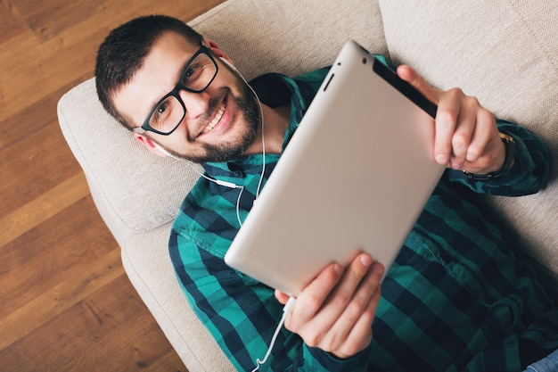 Молодой хипстерский красивый мужчина, лежащий на диване у себя дома, держит планшет, слушает музыку в наушниках, разговаривает онлайн, счастливый, улыбается, зеленая клетчатая рубашка, досуг, очки, вид сверху
