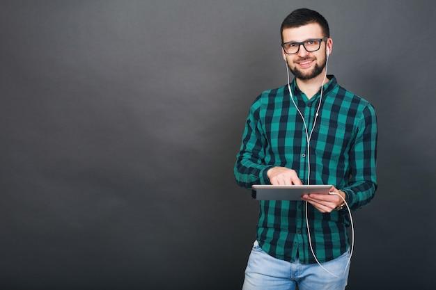 Молодой хипстерский красивый мужчина на сером фоне держит планшет, слушает музыку в наушниках, разговаривает онлайн, счастливые улыбающиеся зеленые клетчатые очки в рубашке, позитивное настроение