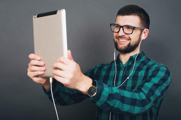 회색 배경에 젊은 힙스터 잘생긴 남자가 온라인으로 말하는 이어폰으로 음악을 들으며 태블릿을 들고 있다