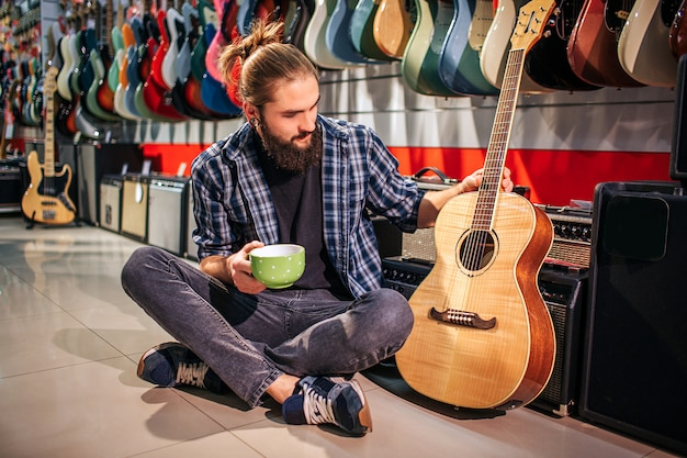 Young hipster has rest by sitting on floor. he hold cup in hand. another one touches acoustic guitar nearby him. young man looks at instrument.