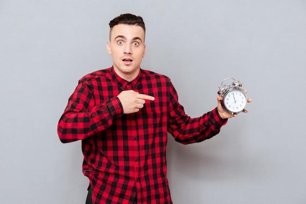 Молодой хипстер в красной рубашке, держа в руке часы и указывая на них. изолированный серый фон