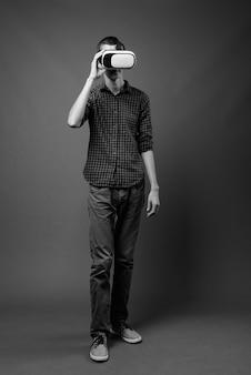 黒と白の灰色の壁に対して若い流行に敏感な男