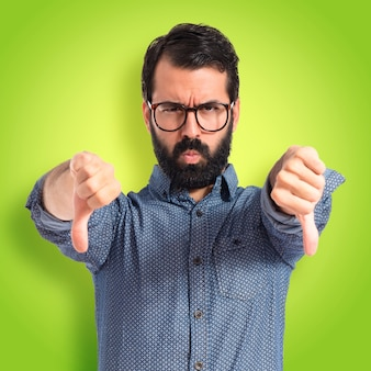 Young hipster man doing bad signal on colorful background