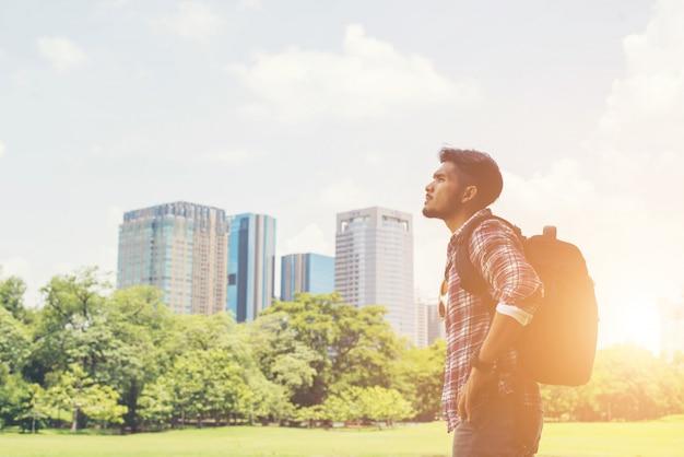 Молодой человек битнику наслаждаться видом города от парка, прежде, чем перейти к тр