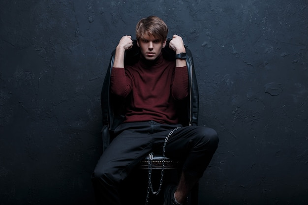 Young hipster man in a fashionable vintage jacket in red golf in stylish jeans in black sneakers with a silver metal chain sits and poses on a chair in a room against the wall. attractive guy