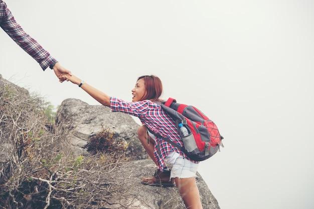 山を登る女性を助ける若いhipster男。