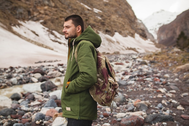 Young hipster man, hiking by the river, wild nature, winter vacation