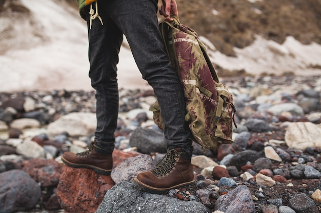 流行に敏感な若い男、川でのハイキング、野生の自然、冬休み、バックパックを手で押し、詳細を閉じる