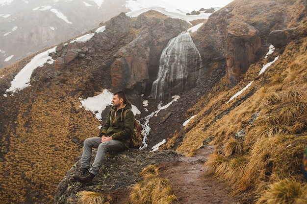 Young hipster man hiking in mountains, autumn vacation traveling