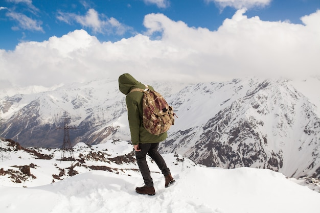 Young hipster man hiking in mountains, winter vacation traveling